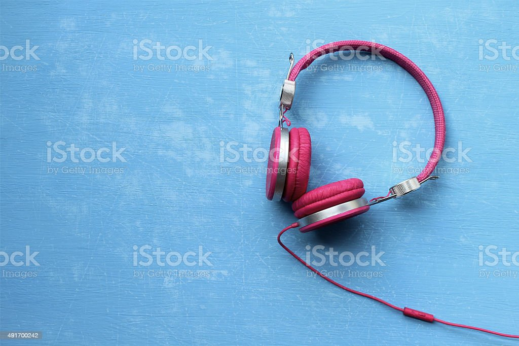 Pink headphones on blue background and grunge effect stock photo
