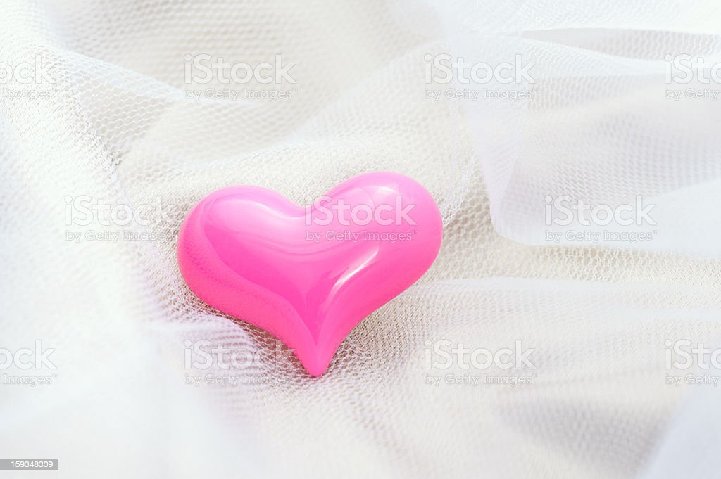 Pink heart on a white veil royalty-free stock photo