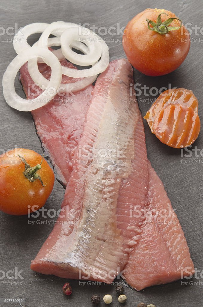 pink herring with vegetable on slate stock photo