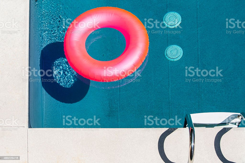 Pink inflatable ring floating in blue pool. stock photo