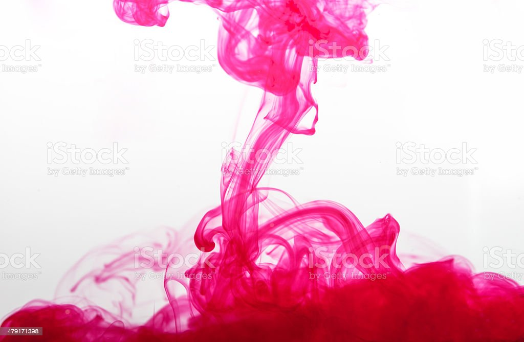 pink ink spread in water stock photo
