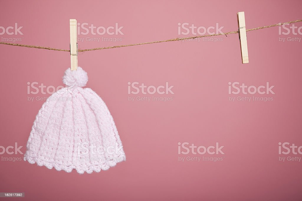Pink Knit Baby Hat Hanging by Clothespin royalty-free stock photo