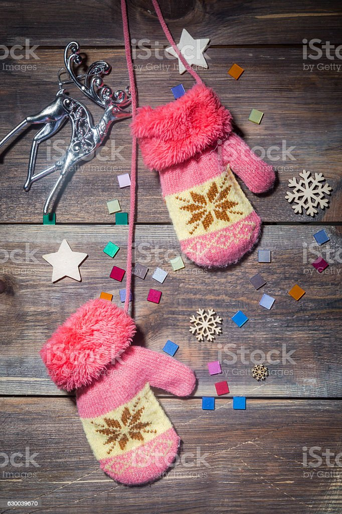pink knitted mittens on a brown wooden Board stock photo