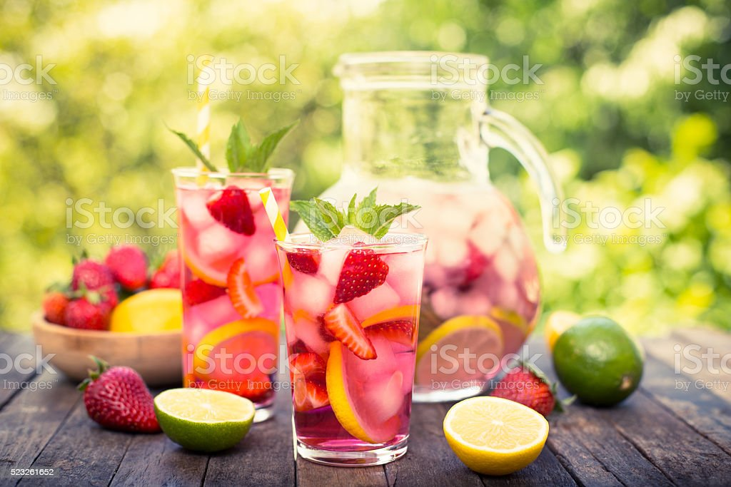 Pink lemonade with lemon, lime and strawberries stock photo