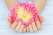 Pink manicure and daisy flower