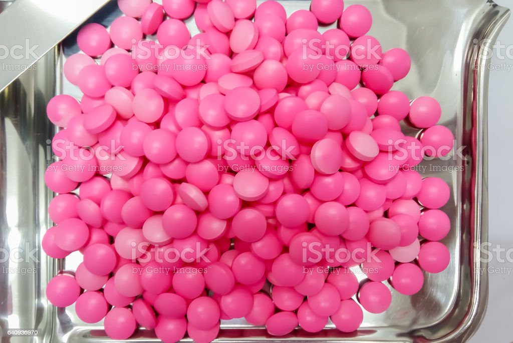 Pink Medicine Capsules on Stainless Steel drug tray, Pills and Spatula stock photo