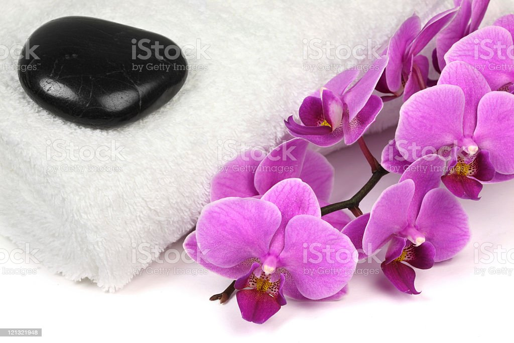 Pink orchid with towel and massage stone royalty-free stock photo