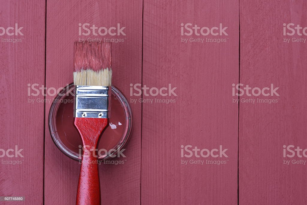 Pink paint can with brush on wooden background stock photo