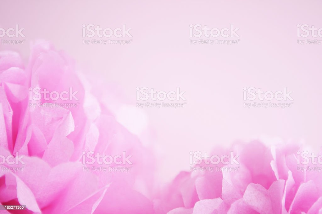 Pink paper pom pons on pink background stock photo