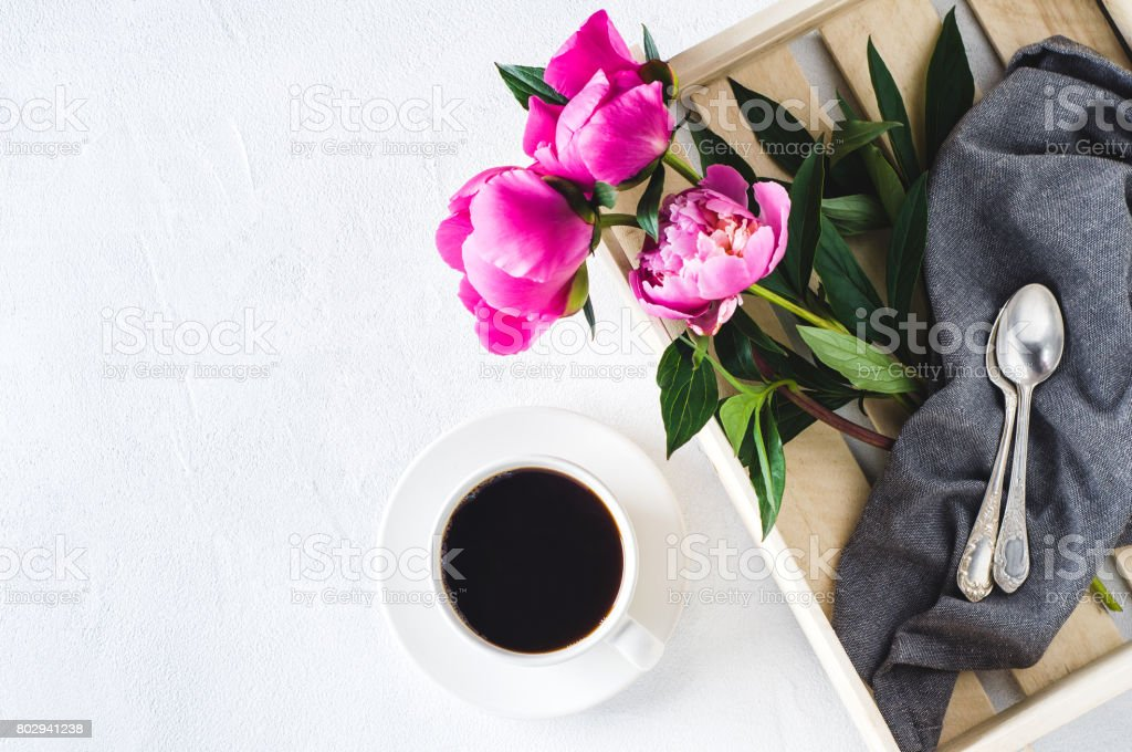 Pink peonies and white cup of coffee on a white concrete background....
