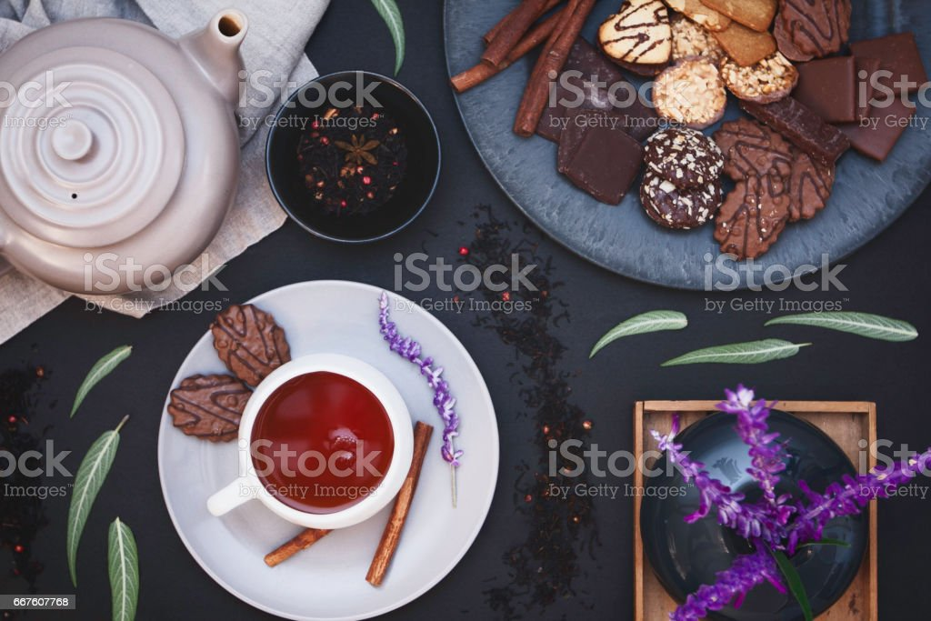 Pink pepper black tea, cookies, spices on dark background form above stock photo