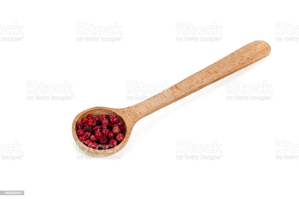 pink pepper in a wooden spoon stock photo