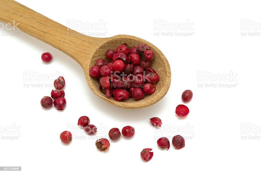 pink peppercorns in a wooden spoon stock photo