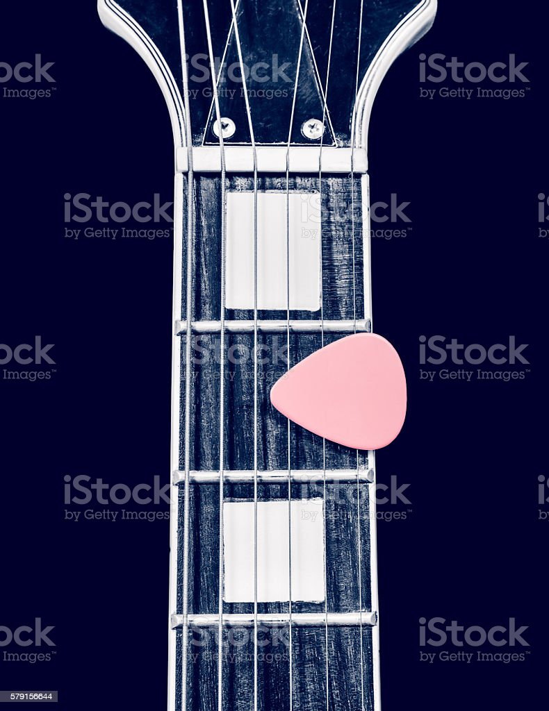 pink pick with electric guitar fingerboard, isolated on black stock photo
