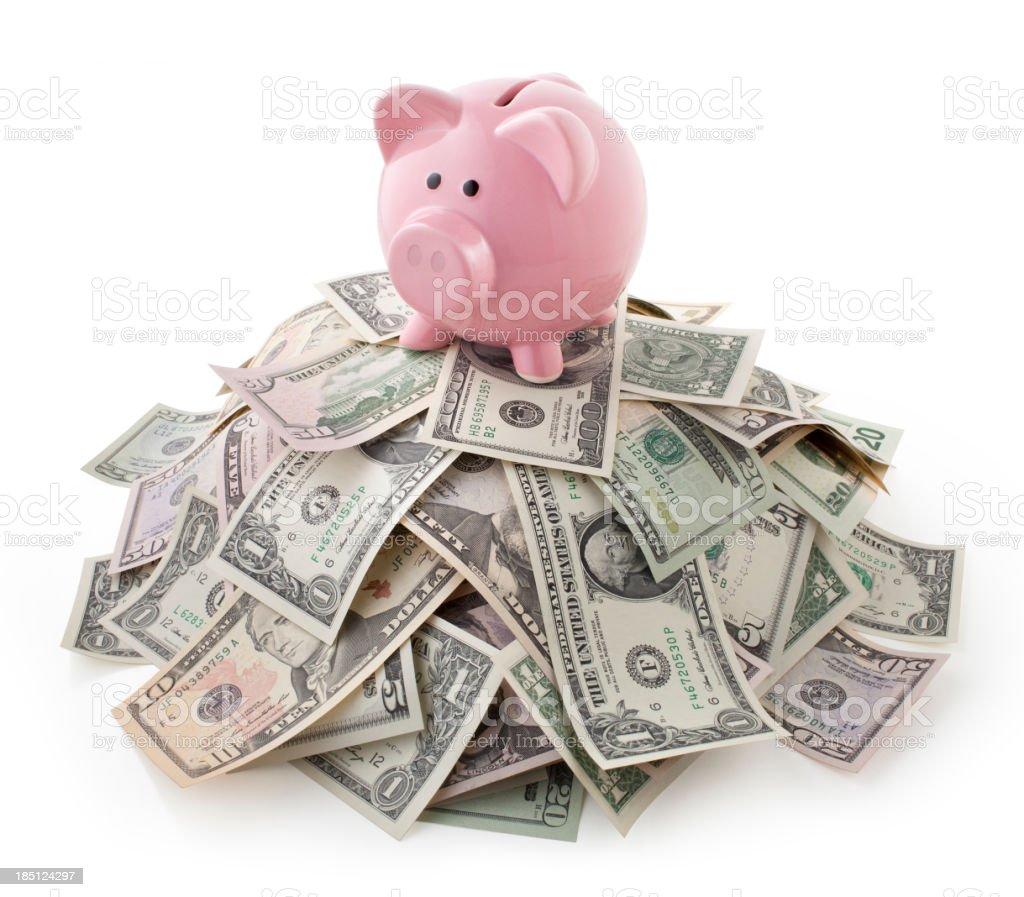 Pink piggy bank on pile of U.S. bills royalty-free stock photo