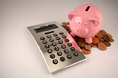 Pink Piggy Bank, Pile of Coins and Silver Calculator