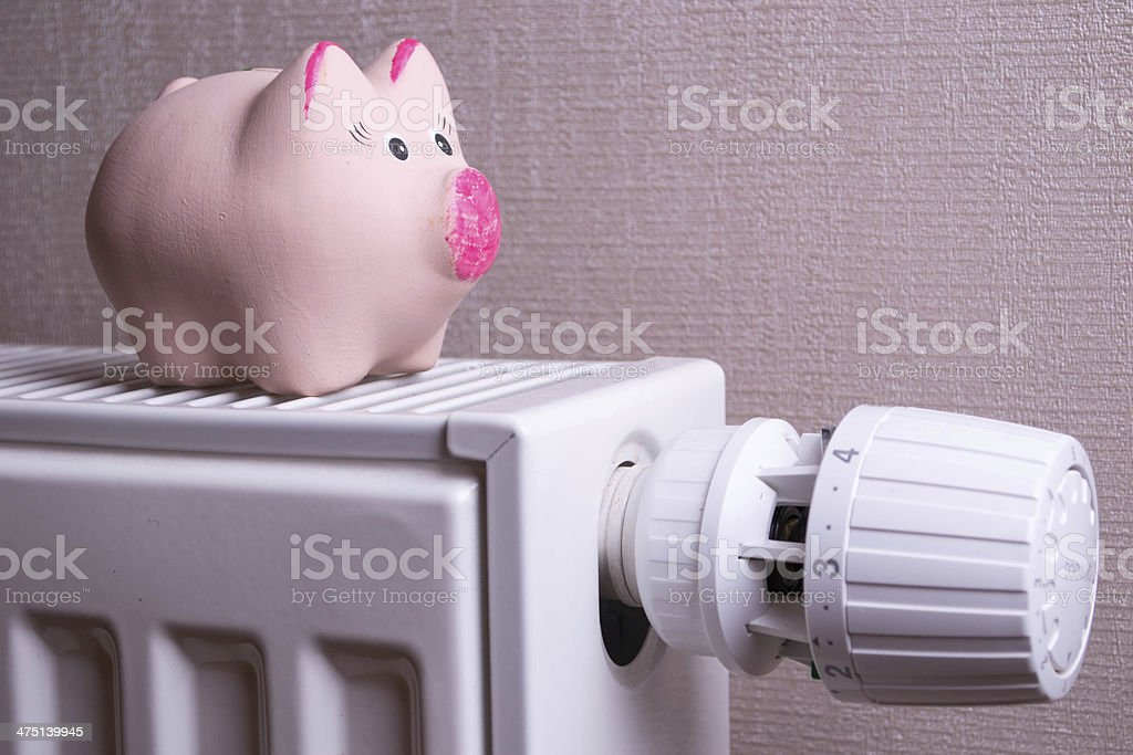 Pink piggy bank saving electricity and heating costs, close up stock photo