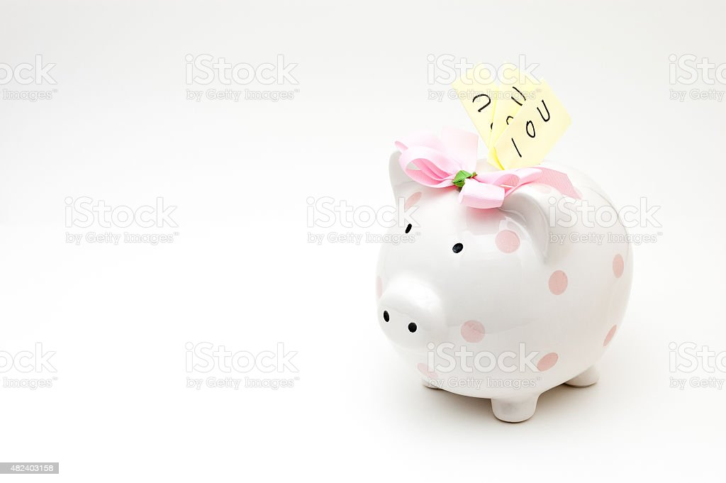 Pink piggy bank stuffed with IOU notes stock photo
