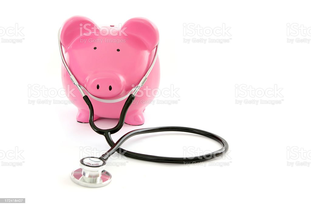 A pink piggy bank with a stethoscope in a white background royalty-free stock photo