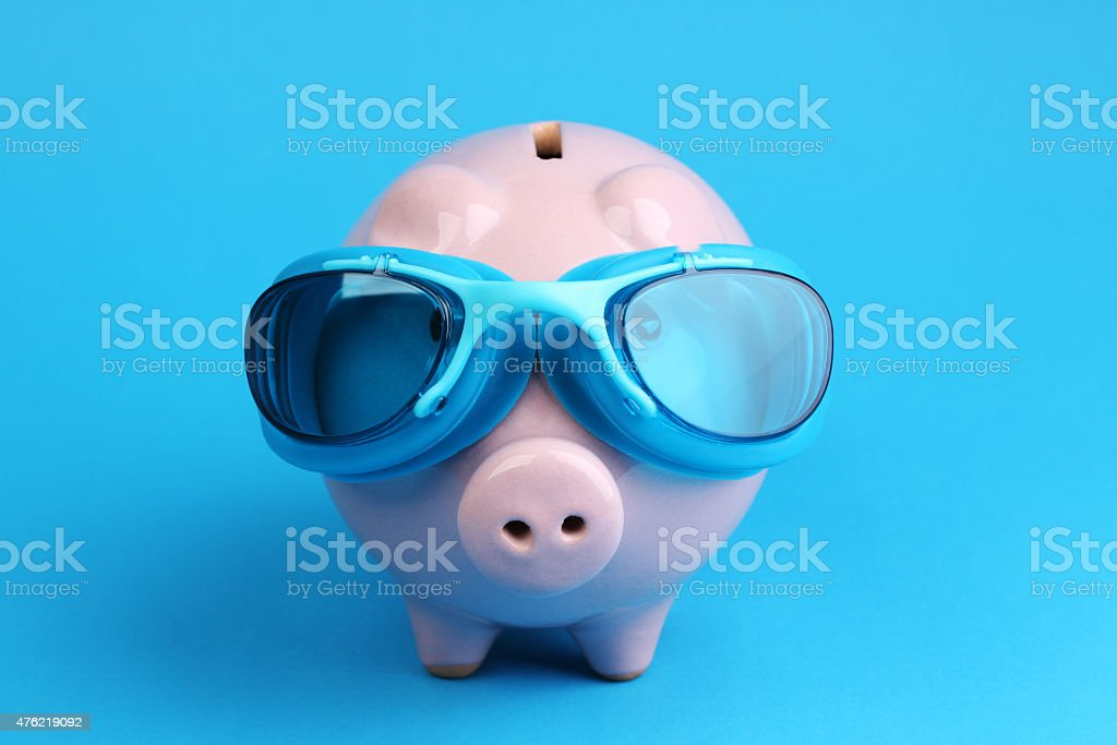 Pink piggy bank with blue swimming goggles on blue background stock photo