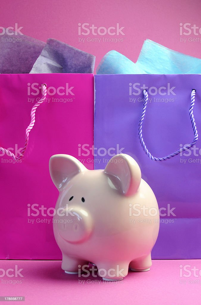 Pink piggy bank with colorful shopping bags. royalty-free stock photo