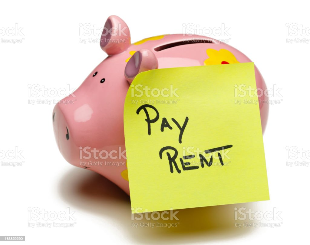 A pink piggybank with pay rent  written on it royalty-free stock photo