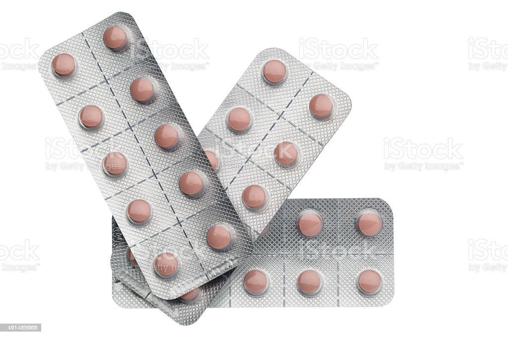 Pink pills packed in blisters isolated on white background stock photo