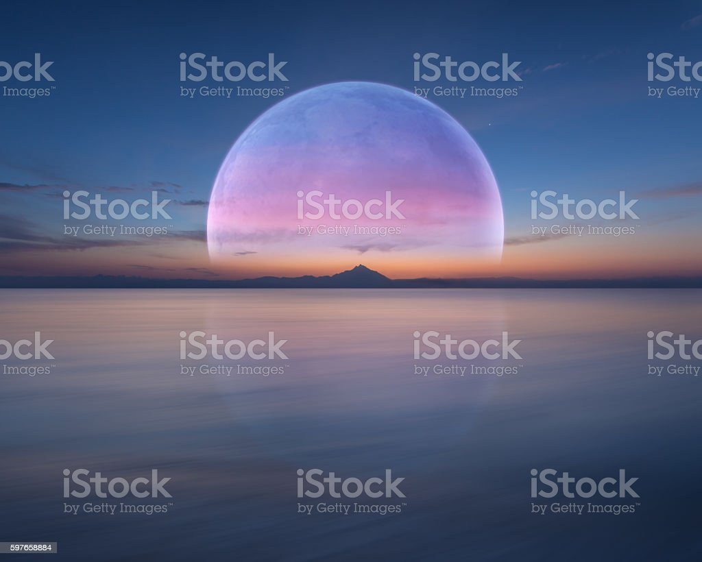 Pink planet like moon above the ocean and mountain stock photo