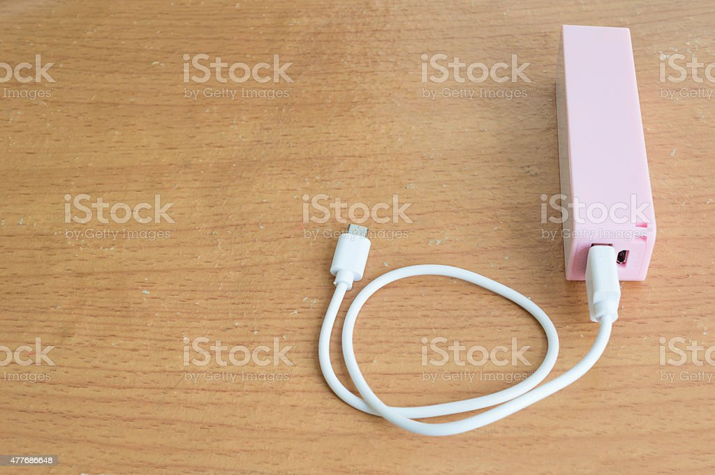 Pink powerbank on wood table and copyspace stock photo