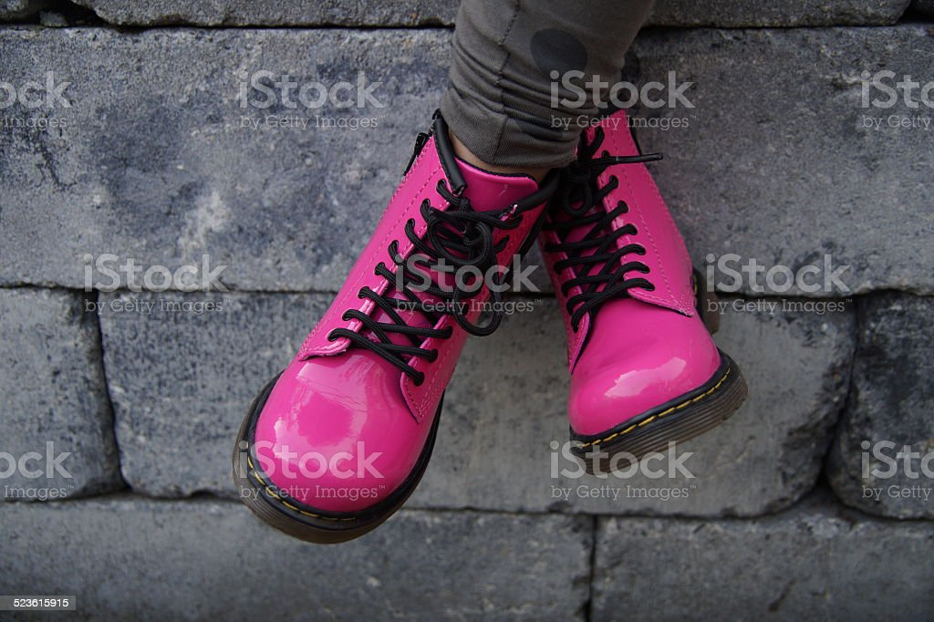 Pink punk alternative girl or woman shoes - cross legged stock photo