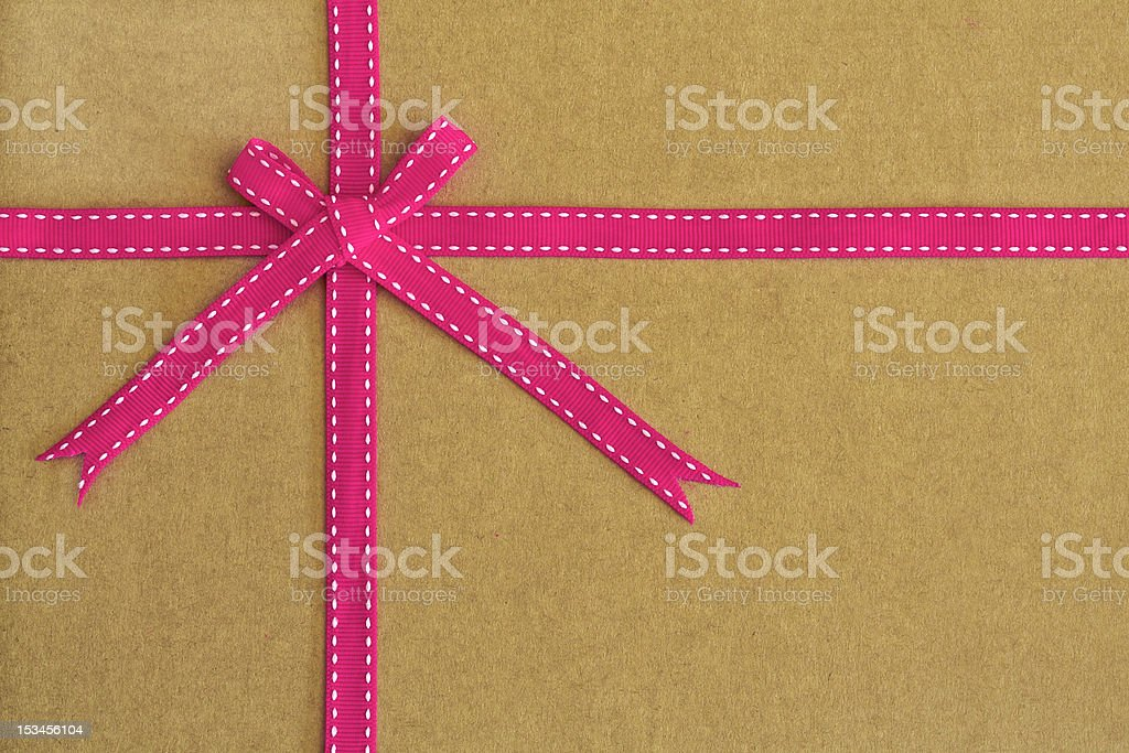 Pink ribbon and bow on recycled card as background royalty-free stock photo