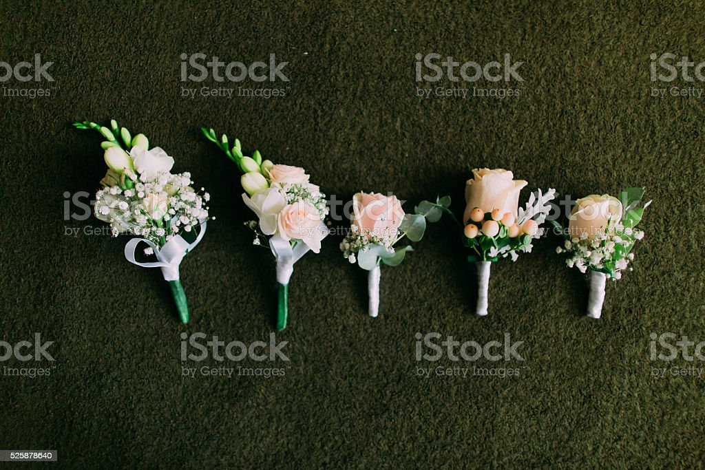 Pink rose boutonnieres on green background stock photo