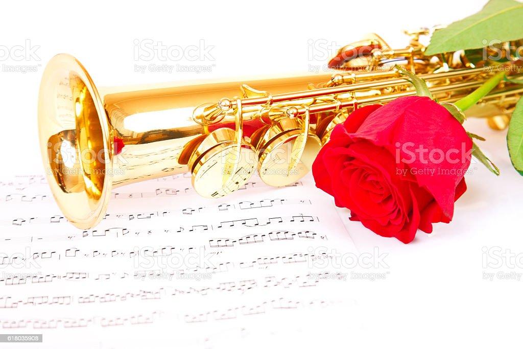 Pink rose, saxophone and music sheet stock photo