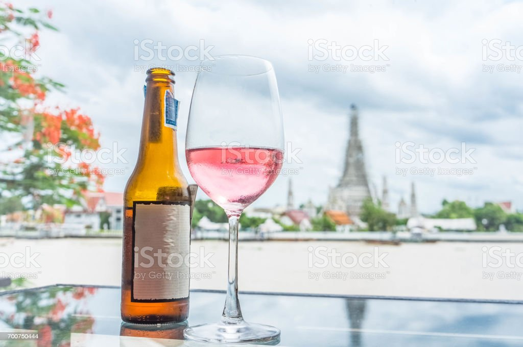 Pink rose wine served on grass table, and wine glass, copyspace for text, blurred background of Wat Arun, Bangkok, Thailand. stock photo
