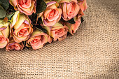 Pink roses bouquet on woven background