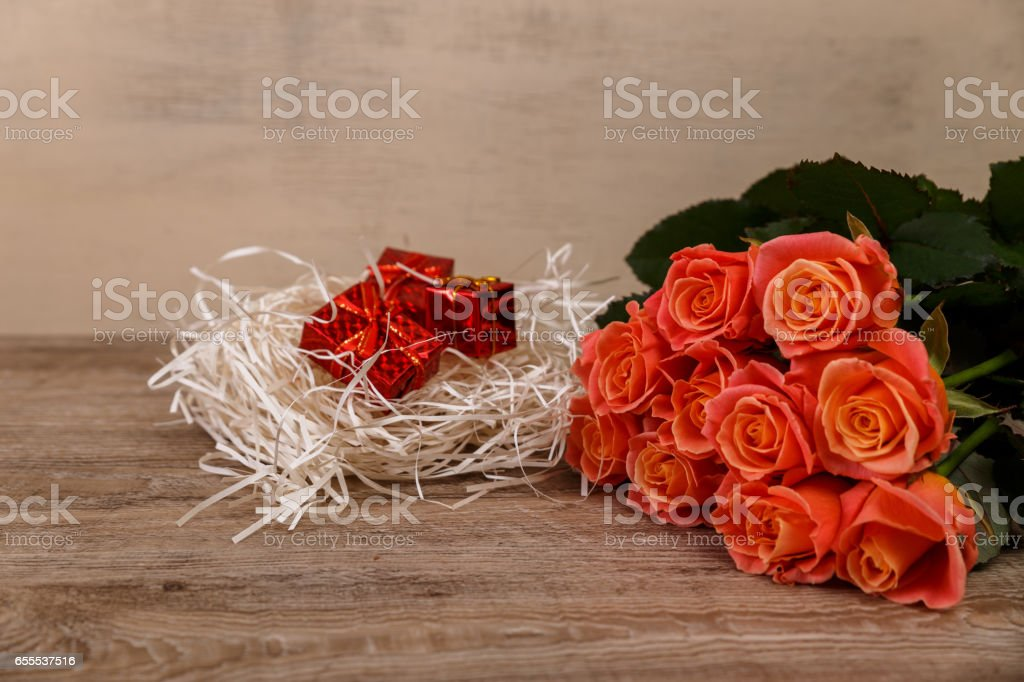 Pink roses with gift boxes on wooden background. stock photo