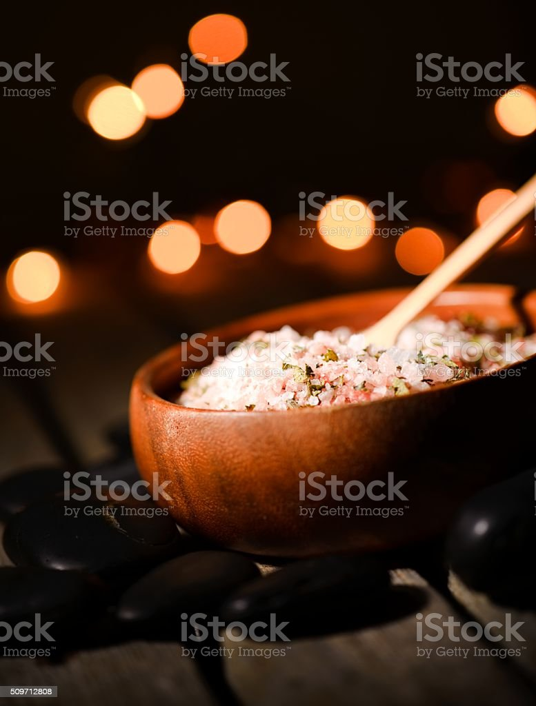 Pink sea salt with herbs in bowl with backlights stock photo