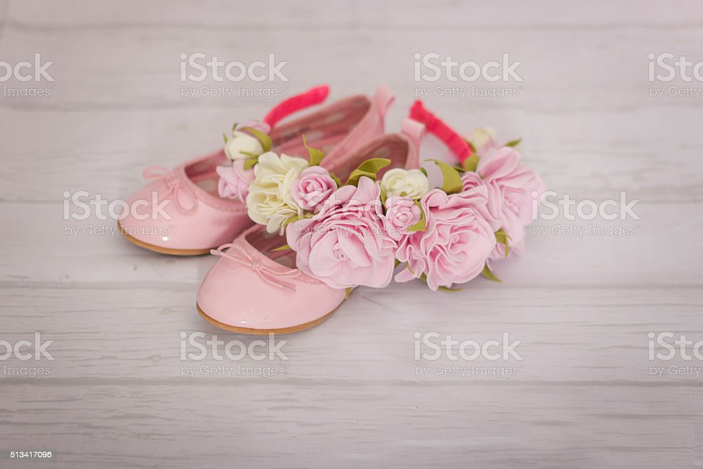 pink shoes for a little girl and flowers headband stock photo