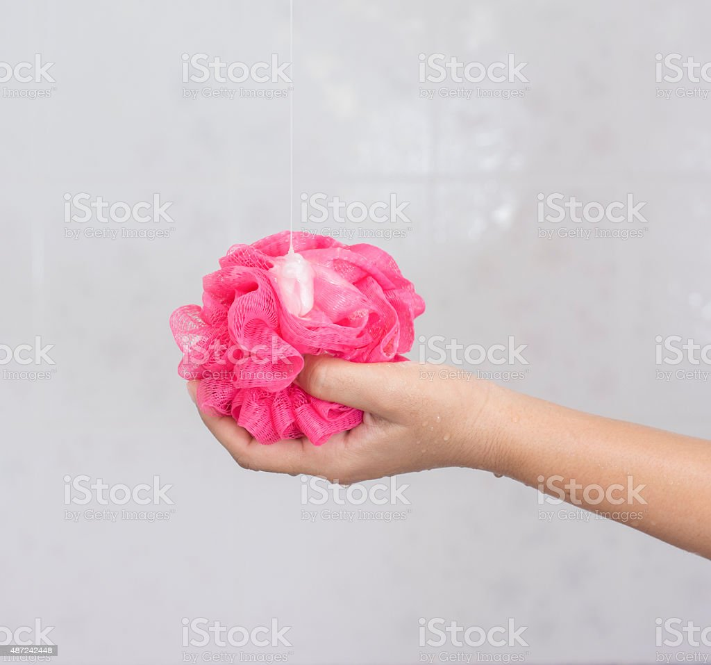 Pink shower sponge with soap in the hand. stock photo