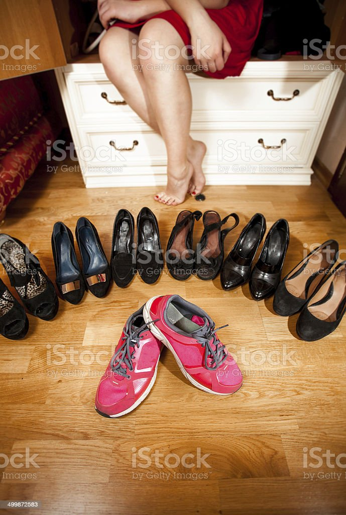 pink sneakers among black high heeled shoes at wardrobe royalty-free stock photo