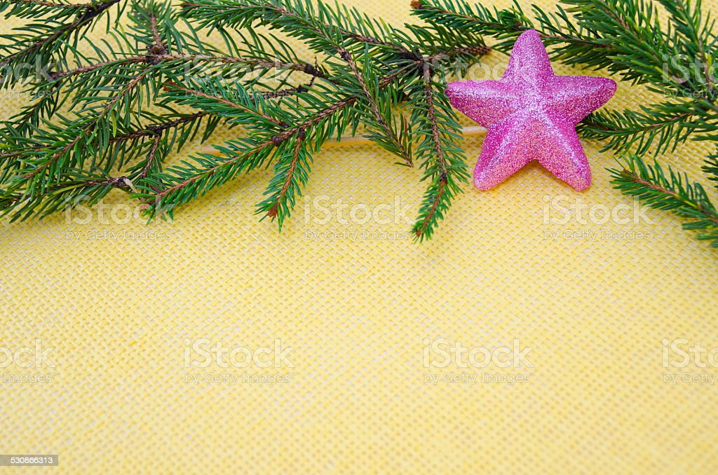 Pink star ornament with fir branches on yellow royalty-free stock photo