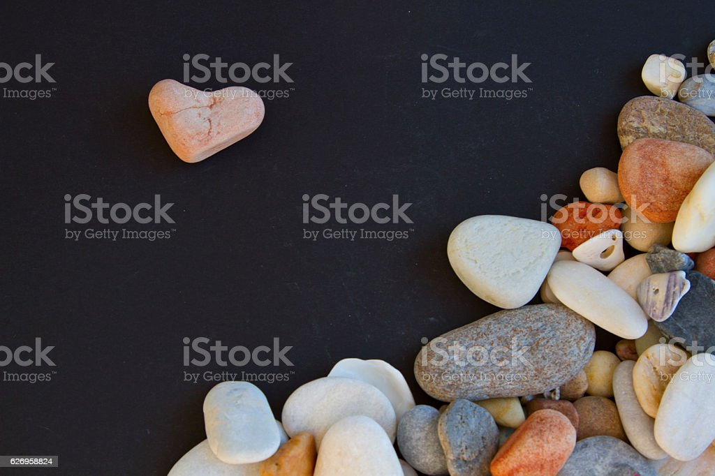 Pink stone like heart shape and a lotof different pebble stock photo