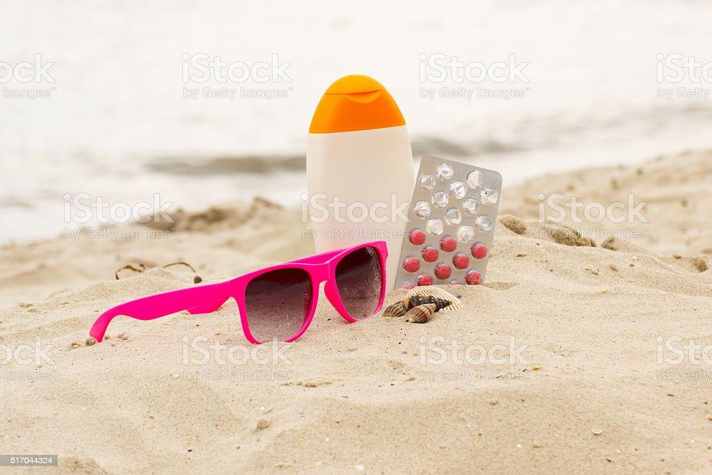Pink sunglasses, shells, lotion and pills of vitamin E stock photo
