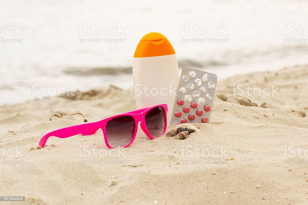 Pink sunglasses, shells, lotion and pills of vitamin E stock photo