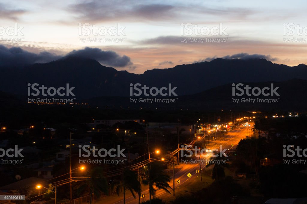 Pink sunrise with dark mountains and traffic lights in foreground stock photo