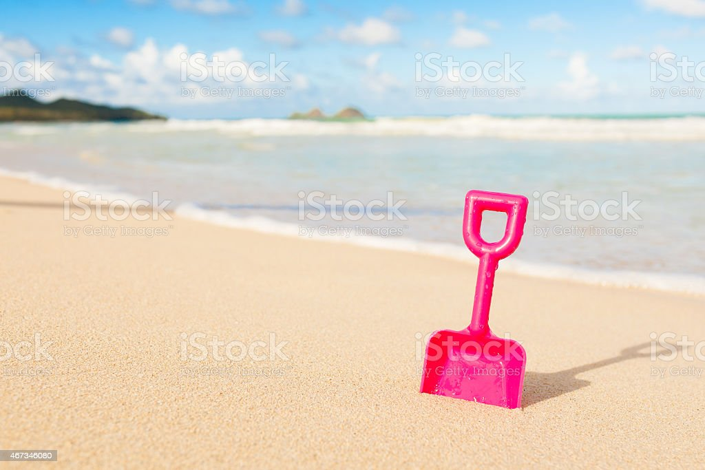 Pink toy shovel stuck on the sand stock photo
