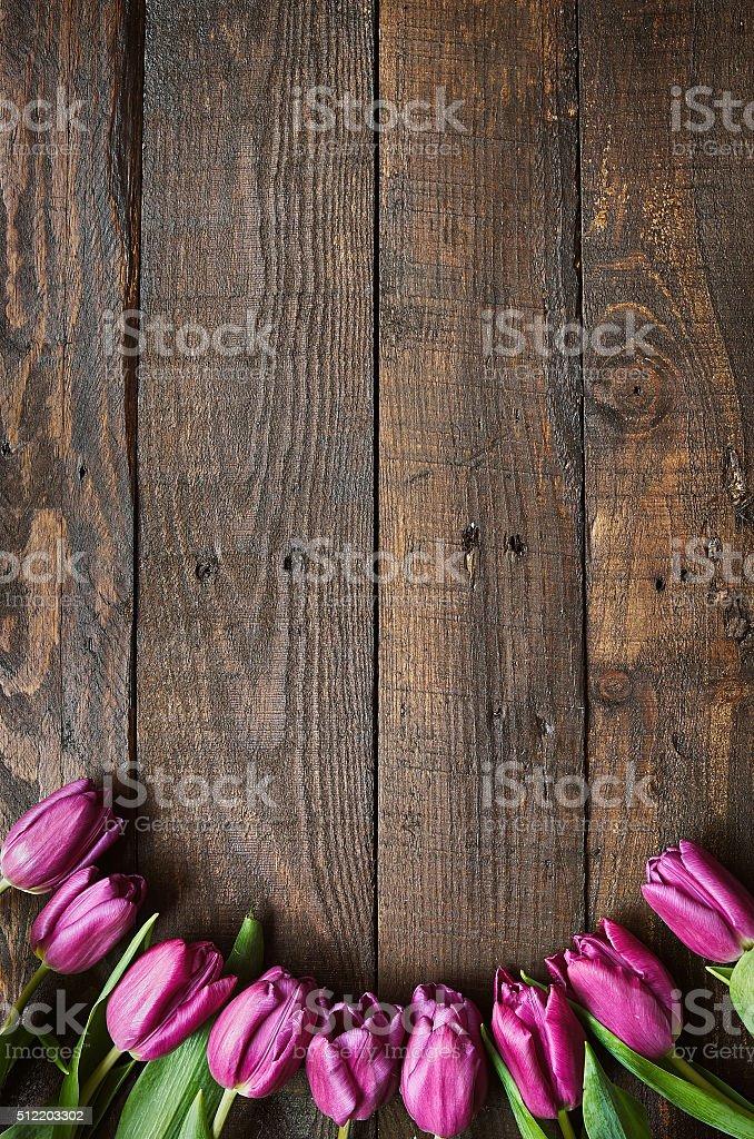 Pink, tulips bunch on dark barn wood planks background stock photo