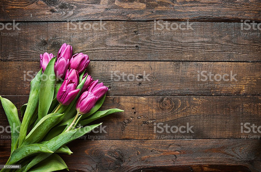 Pink, tulips bunch on dark barn wood planks background stock photo