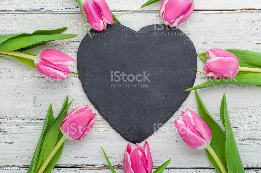 Pink Tulips with an empty heart shaped chalkboard stock photo