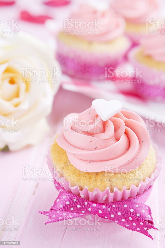 Pink Valentine cupcakes on a rustic pink table royalty-free stock photo